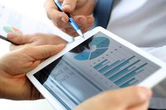 Business colleagues working and analyzing financial figures on a digital tablet Stock Photos