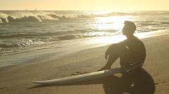 A young male surfer sitting on the beach looking out towards the ocean. Stock Footage