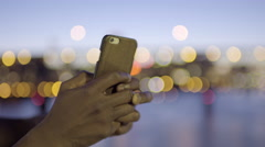 Closeup Of Man's Hands Holding Smartphone and Texting, City Lights In Background Stock Footage