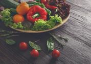 Dish of fresh vegetables on wooden background with copy space Stock Photos