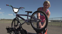 A young woman bmx rider preparing bike. Stock Footage