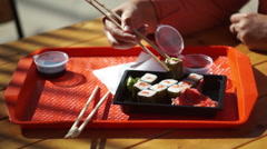 Sushi sets. Human hand dips a sushi by chopsticks in a soy sauce cup Stock Footage