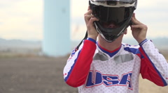A young man bmx rider sitting on bike while putting on helmet. Stock Footage