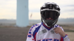 A young man bmx rider sitting on bike while taking off helmet. Stock Footage
