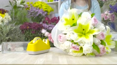 Dolly shot of florist woman wrapping a flower bouquet with paper Stock Footage