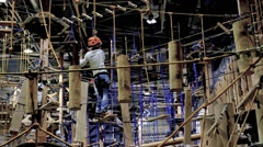 Children age 6-12 attend indoor adventure climbing park Stock Footage