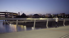 Man Goes For An Evening Walk Across Pedestrian Bridge Over River In City Stock Footage