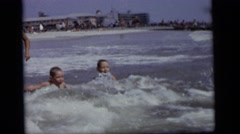 1964: two children taking pleasure of bathing in a sea beach with their guardian Stock Footage