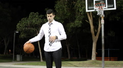 A young business man dribbling a basketball after work on an outdoor court at ni Stock Footage