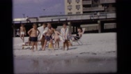 1964: a group of children at a sandy beach go in and come out the water  Stock Footage