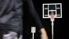 A young man shooting three-pointers on an outdoor basketball court at night. Stock Footage