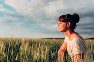 Girl sits in a meadow Stock Photos