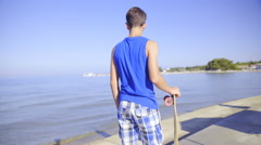 Teenager with longboard under hand looking around the beach 4K Stock Footage