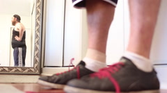An out of shape man tying his shoes before working out. Stock Footage