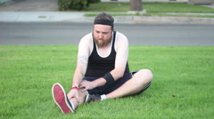 An out of shape man stretching in the grass before working out. Stock Footage