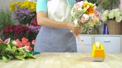 Florist woman tying ribbon on a beautiful flower bouquet Stock Footage