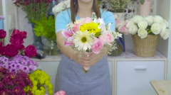 Florist woman giving a beautiful flower bouquet to the camera Stock Footage