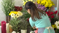 Florist woman taking care all of beautiful blooming flowers in flower shop Stock Footage