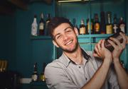Young handsome barman in bar shaking and mixing alcohol cocktail Stock Photos