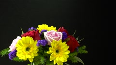 Close up shot of spraying water on a beautiful flower bunch, black wallpaper Stock Footage