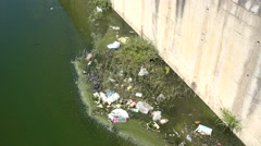 Litter and green water in drainage ditch Stock Footage