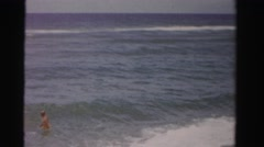 1955: working hard to keep their footing in the crashing waves of the ocean. Stock Footage