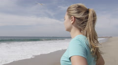 A woman runner resting on the beach after her run. Stock Footage