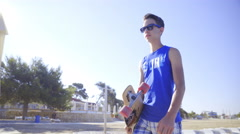 Boy walking at beach holding longboard 4K Stock Footage