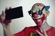 Evil clown taking a selfie Stock Photos