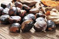 Roasted chestnuts on a rustic wooden table Stock Photos