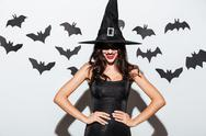 Happy gothic woman in witch halloween costume standing and smiling Stock Photos