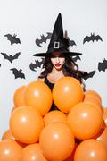 Attractive young woman in witch halloween costume with orange balloons Stock Photos