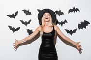 Beautiful blonde young woman in witch costume standing and laughing Stock Photos