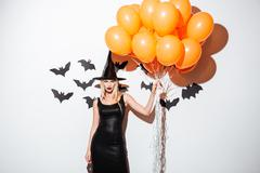 Sexy young woman in witch halloween costume holding orange balloons Stock Photos