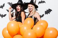 Two happy women in witch halloween costumes with orange balloons Stock Photos