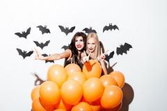 Two smiling women with vampire makeup and balloons having fun Stock Photos