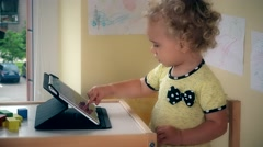 Serious child using tablet computer sitting near table Stock Footage