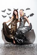 Two cheerful young women with halloween vampire makeup on party Stock Photos