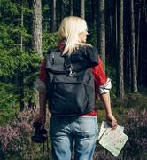 Young active woman tourist standing in a clearing in the woods with  backpack Stock Photos
