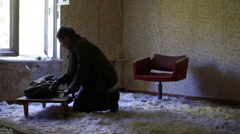 Killer in the post apocalyptic clothing comes in an abandoned room, strewn with Stock Footage