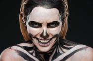 Smiling young woman with skeleton halloween makeup laughing Stock Photos