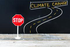 Mini STOP sign on the road to CLIMATE CHANGE Stock Photos