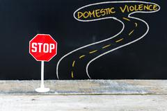 Mini STOP sign on the road to DOMESTIC VIOLENCE Stock Photos