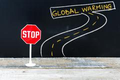Mini STOP sign on the road to GLOBAL WARMING Stock Photos