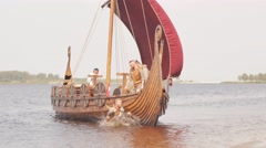 Mad vikings warriors in the attack, running along the shore with Drakkar on the Stock Footage