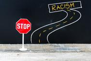 Mini STOP sign on the road to RACISM Stock Photos