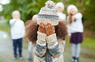 Crying girl hiding her face while classmates mocking at her Stock Photos