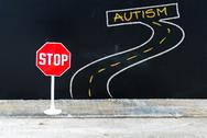 Mini STOP sign on the road to AUTISM Stock Photos