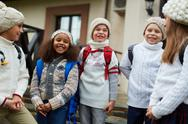 Group of happy schoolkids in knitted caps and sweaters Stock Photos