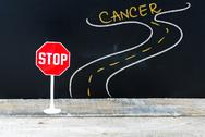 Mini STOP sign on the road to CANCER Stock Photos